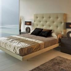Dormitorio de diseño con cabezal y aro cama tapizados y mesitas de tres cajones en roble