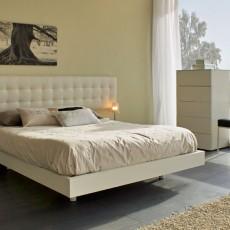 Dormitorio de diseño con cabezal mesita y aro cama blanca